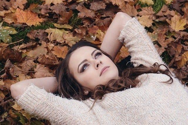Nainen makaa lehtien päällä